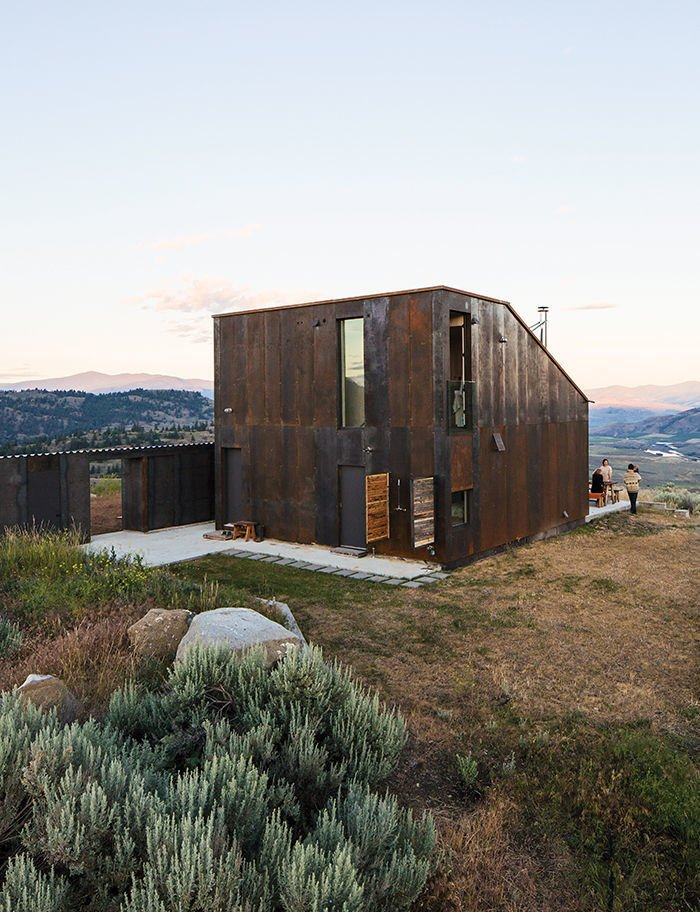 Exterior, Metal, Metal, Saltbox, Cabin, House, and Tiny Home Architect Jesse Garlick's rural Washington vacation home references its rugged surroundings. The steel cladding has developed a patina similar to the ochre-red color of bedrock found in the area.  Exterior Metal Saltbox Cabin Photos from Sky House