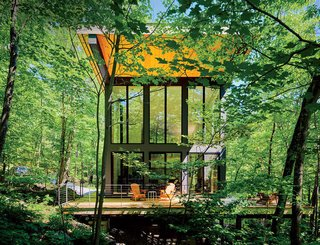 A cantilevered cabin designed by R D Gentzler blends into the forest, even as it hovers above a 20-foot drop-off. Its south face is almost entirely glass, but a roof canopy limits solar gain.
