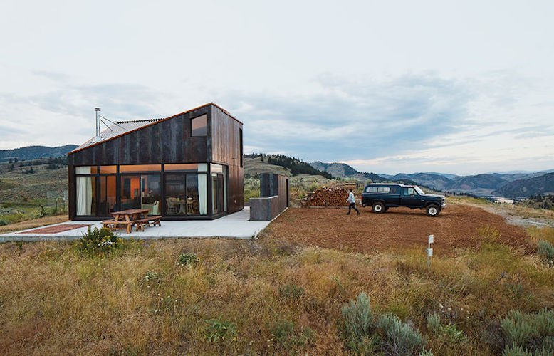 Back Yard, Grass, Shrubs, Exterior, House Building Type, Metal Roof Material, and Metal Siding Material A narrow building next to the main structure houses storage and an outdoor kitchen.   Photos from Sky House