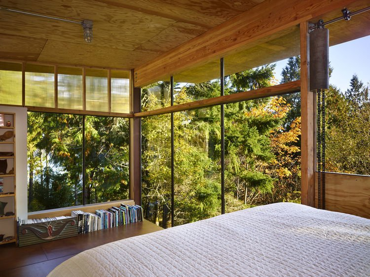 In the sleeping loft, floor-to-ceiling windows overlook the fir canopy of the surrounding forest.   Scavenger Studio