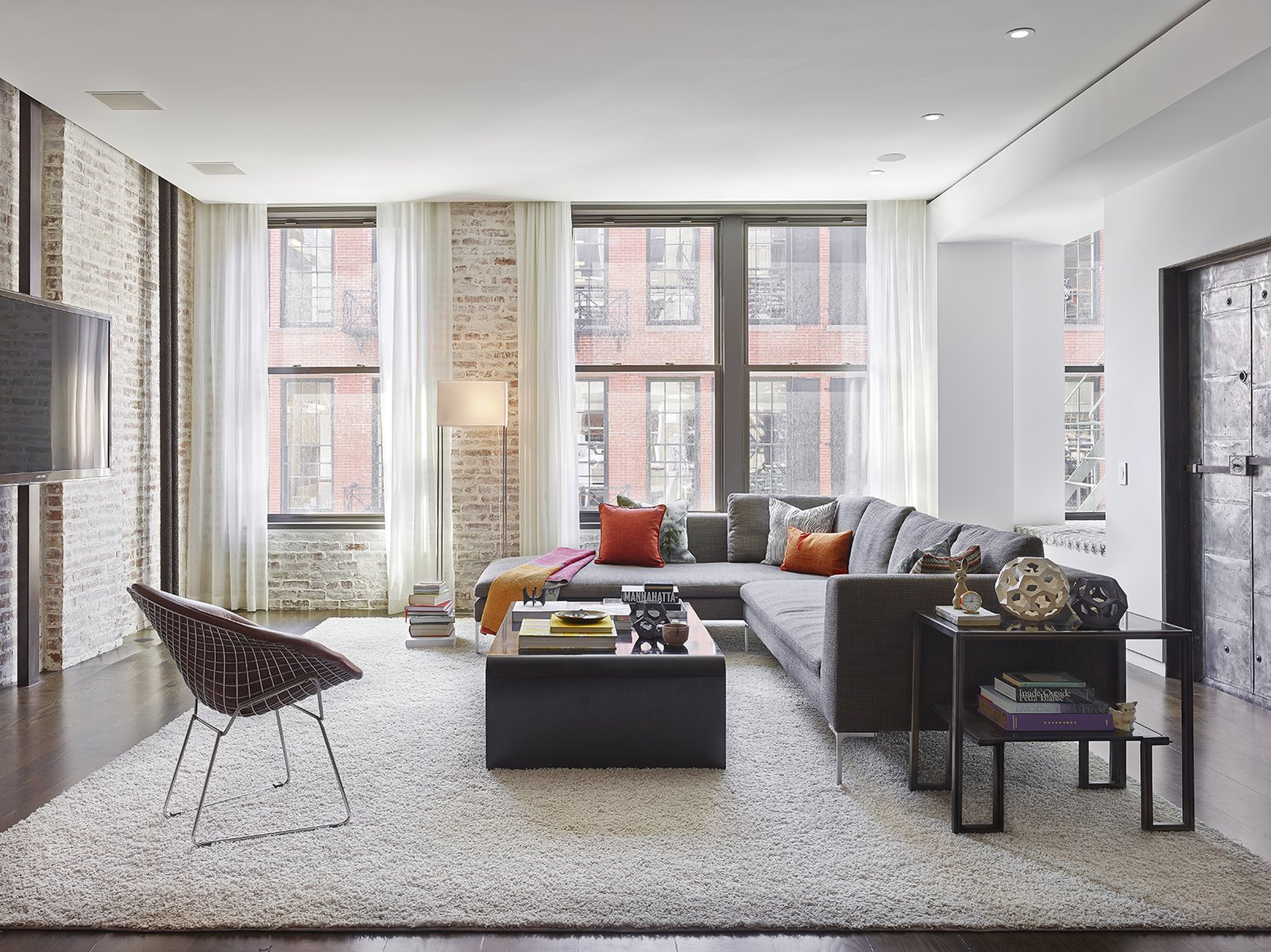 The residence is located on Crosby Street, which is part of the landmarked SoHo Cast Iron Historic District. Once a manufacturing and industrial area then an artists' enclave, the neighborhood is now a retail hub. This particular loft used to be a light bulb factory, which informed the renovation's materiality. All of the natural light enters the apartment from the living room windows. 590BC worked with Tamara Eaton Design to furnish the interiors, which holds a mix of refined and rough-hewn pieces. A vintage Harry Bertoia chair holds court with a B&B Italia sofa, shag carpet by Shansom Rugs, steel side table from Global Views, and steel Arco coffee table from Room. Throw pillows upholstered in fabrics from Upstate, Maharam, and Romo add punches of color. Photo by Frank Oudeman.  exposed brick from A Renovated Loft in SoHo