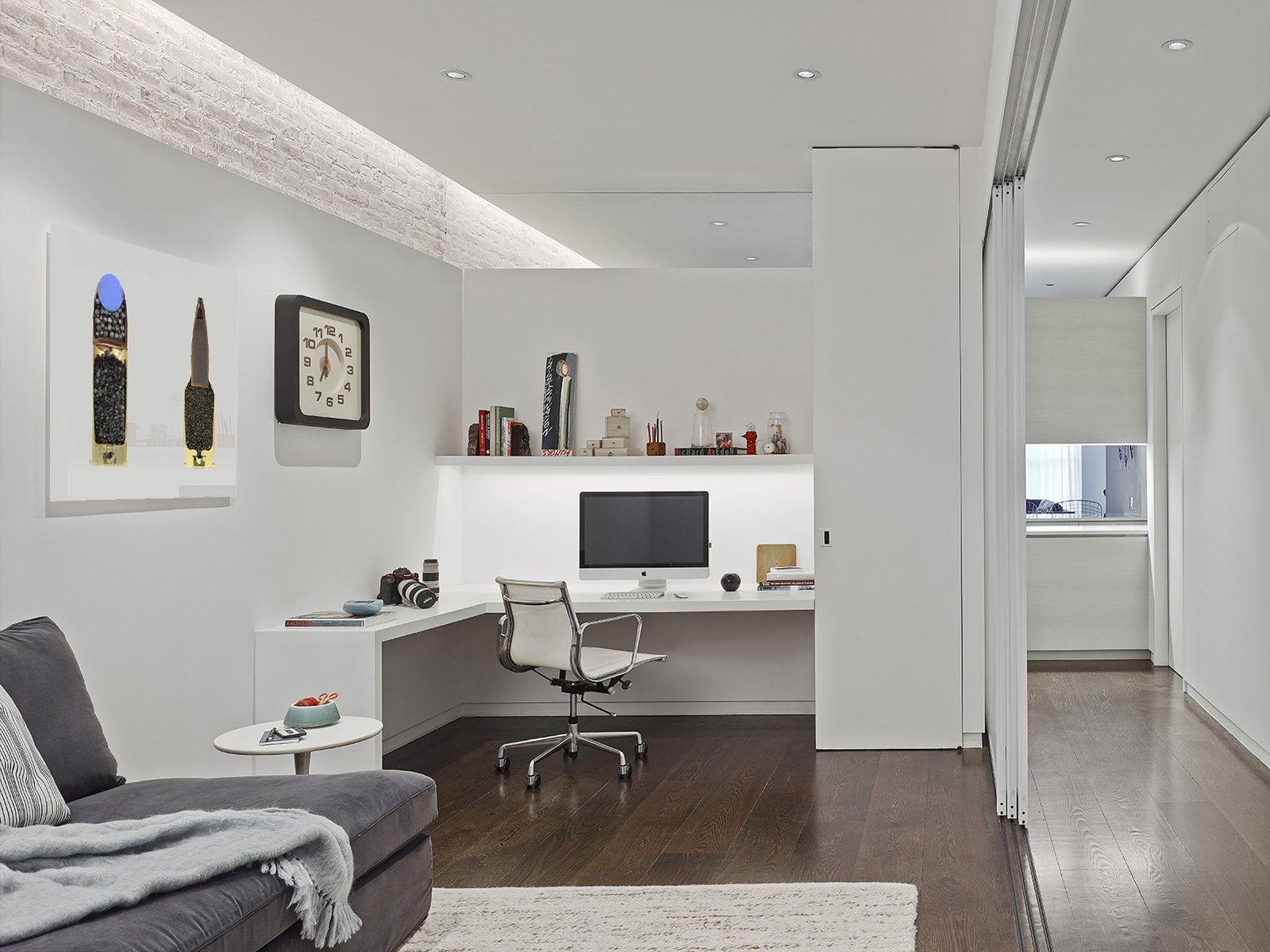 590BC got creative with lighting solutions for the space. The firm advises varying the light sources and details to help make dimly lit spaces feel bright. In the office, linear LED fixtures housed within ceiling coves reflect light down the brick walls. Ceiling fixtures illuminate the space as does lighting installed under the built-in shelving. Photo by Frank Oudeman.  Office from A Renovated Loft in SoHo