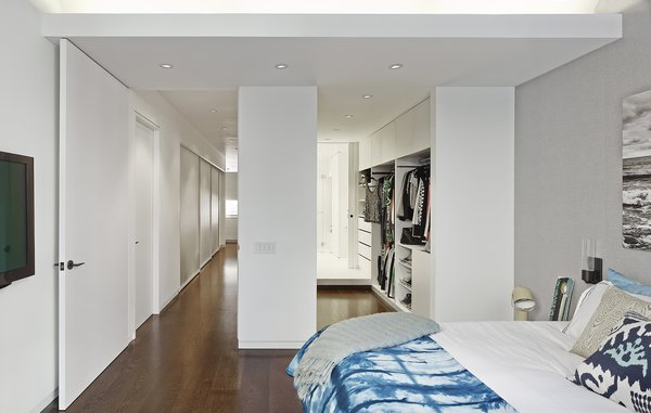 """In the bedroom, an open closet with built-in shelving leads to the master bathroom. Thinking of all the loft's components as part of a whole was critical to the renovation. """"The space is clean and simple, but that is only possible because of the attention paid to eliminating visual clutter that often comes from typical detailing,"""" Breitner says. """"The HVAC, floor outlets, door detailing, wall reveal base, recessed glazing channel, and radiator covers could look like clutter. We integrated it into the architecture."""" Photo by Frank Oudeman."""