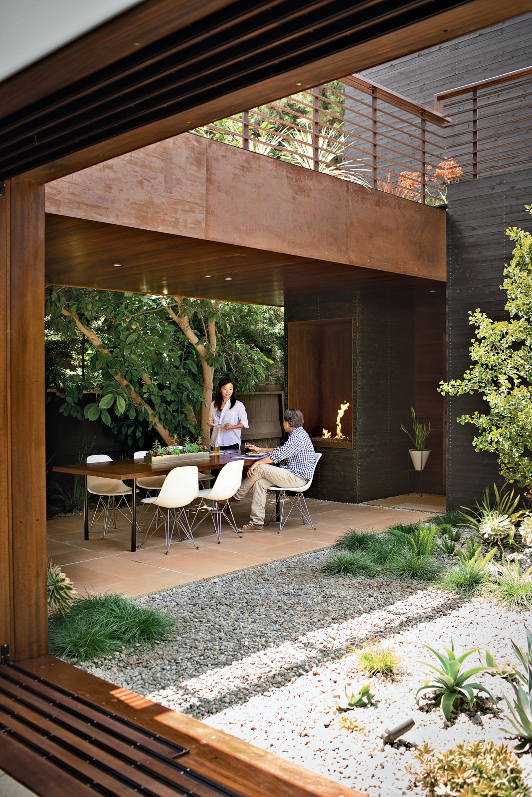 Outdoor, Back Yard, Trees, Shrubs, Hardscapes, Small, Raised Planters, Tile, and Landscape The couple often dine on the patio off the kitchen, warmed by a fireplace from Spark Modern Fires. Photo by Coral von Zumwalt.  Best Outdoor Landscape Photos from A Modern Bungalow in Venice Beach