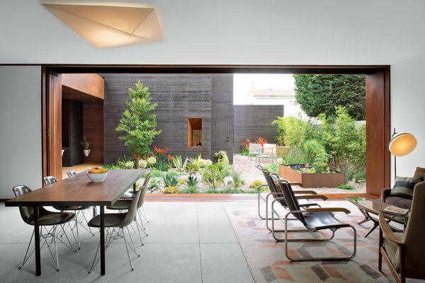 The living and dining room look out to the central courtyard, promoting indoor/outdoor living. Here, five doors slide into a pocket in the wall to create a nearly 23-foot-wide opening on one side looking into the garden. Another set on the opposite side enhances cross ventilation.