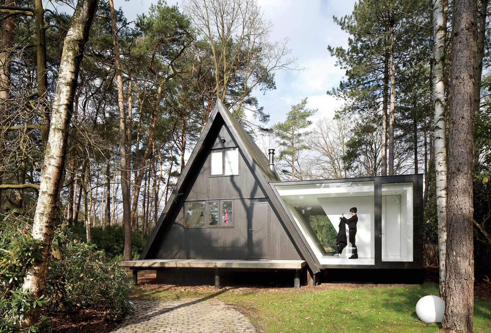 Exterior, Glass Siding Material, Cabin Building Type, A-Frame RoofLine, House Building Type, and Wood Siding Material Adding 290 square feet to this already small (just 566 square feet) black A-frame in Brecht, Belgium, was all the local building ordinances allowed, but the architects at dmvA found that a single wing extended out to the side gave resident Rini van Beek all the storage and living space that she needs.  Best Photos from A Modern Glass Addition in Belgium
