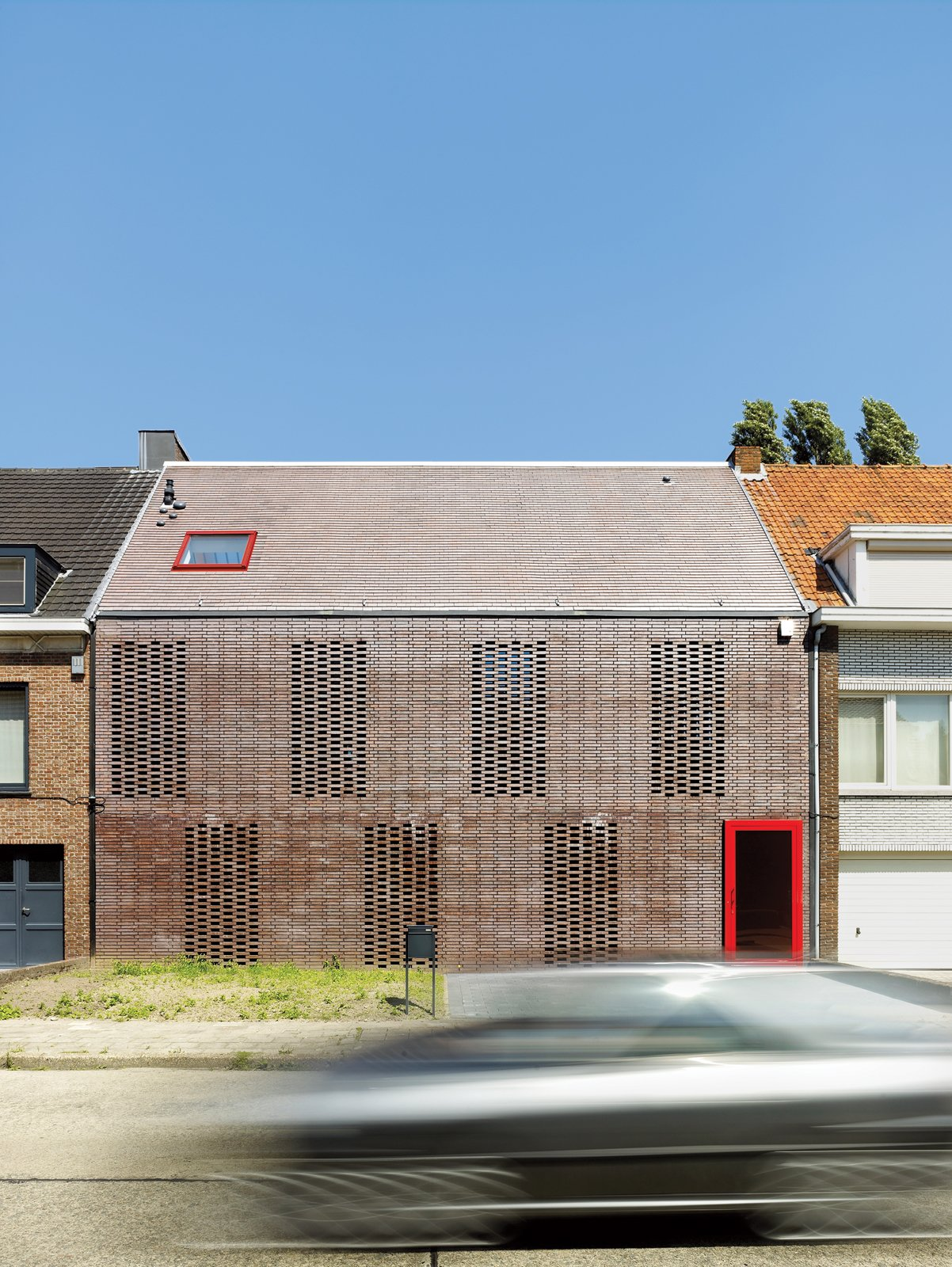 """Exterior, Gable RoofLine, and Wood Siding Material The facade of a house in Belgium consists of """"knitted bricks.""""  """"In this part of Belgium, 90 percent of the houses are built with brick,"""" says architect Tom Verschueren. """"It's a classic material that we tried to use in House BVA in a totally different way.""""  Minimalist Facades We Love by Zachary Edelson from Facade Focus: Brick"""