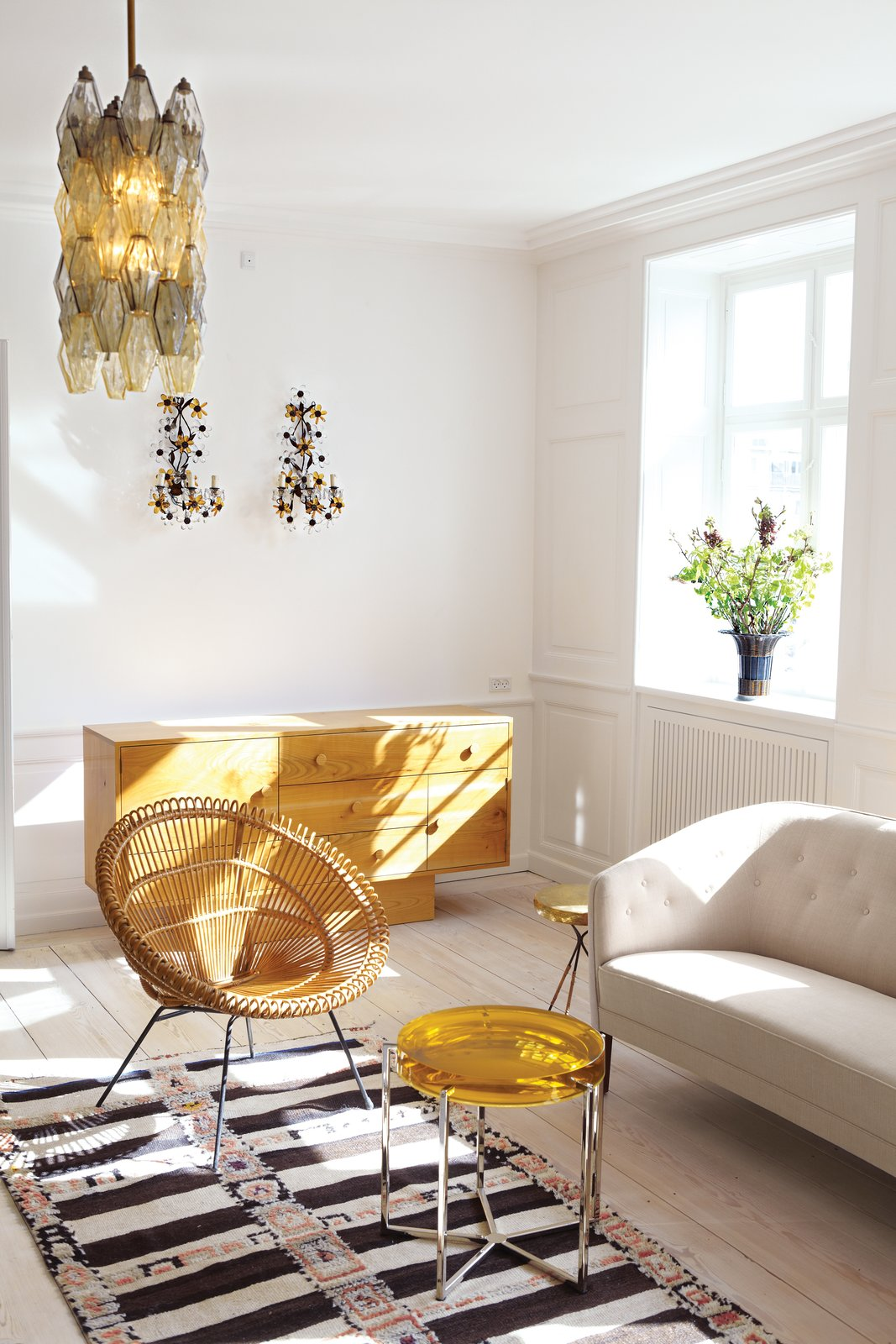 In the living room, furnishings include a cherry-wood dresser by Rune Bruun Johansen, a vintage wicker lounge chair from Italy, and a Ludvig Pontoppidan settee. The round Lens table is by McCollin Bryan. Lighting includes a circa-1950s Venini Poliedri chandelier and French floral wall sconces from the 1930s. Photos courtesy the Apartment.  Modern Danish Homes We Love from A Curated Apartment Turned Showroom in Copenhagen