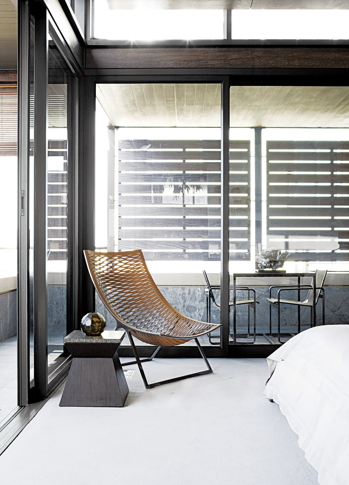 """In the master bedroom, a woven Loom chair by Matteograssi is paired with a wood-and-marble side table from Cécile & Boyd's. Sliding glass doors lead to the screened outdoor veranda with a custom bronze table and Neutra Batyline chairs from Marlanteak. """"The outside-inside flow was important to us, as the apartment is all about views and using the veranda spaces,"""" says designer Geordi De Sousa Costa.  Bedrooms by Dwell from A Sophisticated Penthouse in Cape Town"""