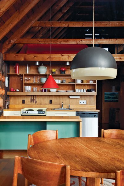 Jens Risom's family retreat in Rhode Island is a pitched prefab with a second-story loft. A no-frills kitchen features wooden shelves that mimic the home's beams. Photo by Floto + Warner.