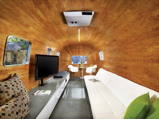 """The long sofa, bar, and television were obvious choices for a pre-show hangout, but how to achieve the continuous curve of the revamped Airstream's interior was not. Baldridge and his team labored to find a kind of wood that would accept the serious bend before hitting on mahogany veneer. As for the new entry, he imagined it as a """"modern I Dream of Genie bottle."""""""