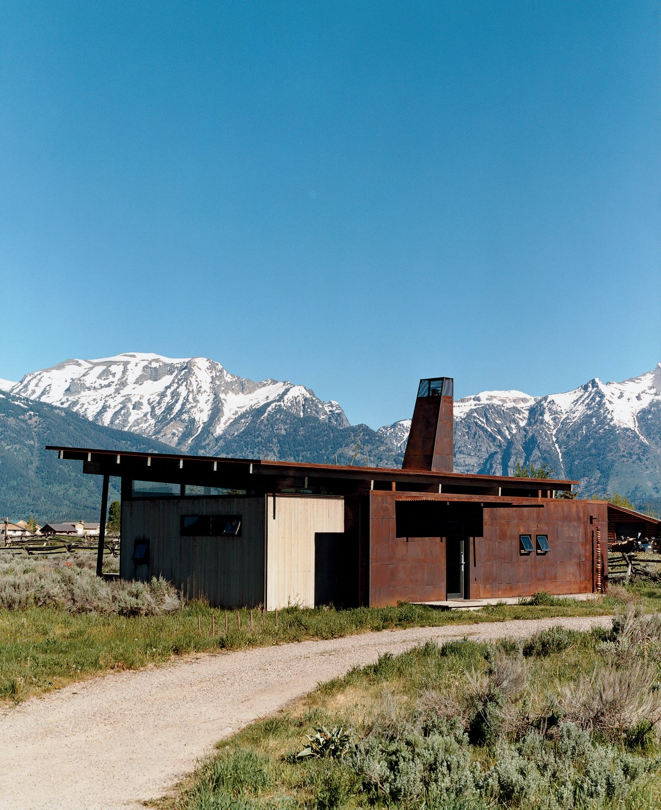 Exterior, House Building Type, Metal Siding Material, Shed RoofLine, and Cabin Building Type Eric Logan's guest house is adjacent to his family's home. The interiors are made up of oiled masonite wall paneling, raw MDF cabinetry, and an oiled concrete floor.  Small Spaces in Rural Places by Kate Santos from Jackson, WY