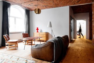 By burnishing historic details and adjusting the floor plan, multidisciplinary studio Loft Szczecin restored and transformed a loft in a warehouse that dates from before World War II. The living room rug is a Polish textile from the 1930s.