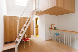 A lofted sleeping pod offers a bit of privacy and helps maximize space. Beneath it is a zippy yellow bathroom.