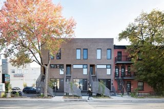 A light grey-brown brick facade provides a contemporary aesthetic in Montreal's Rosemont-Petite-Patrie neighborhood. Developer Maitre Carre and the firm Architecture Open Form worked together to introduce a contemporary style to the area. The project includes three two-story town houses and three above with a mezzanine and rooftop patio.