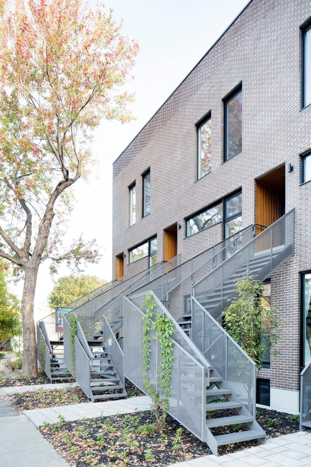 Exterior and Brick Siding Material Plants wrap around the perforated aluminum railings for a natural touch.  Best Photos from Meet Your New Neighbors: Minimal Town Houses with Character