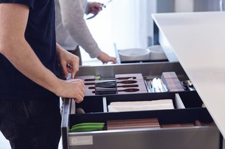 Their systems include award-winning components like the Drawer Accessory System, shown here with a construction of Paperstone and solid surface acrylic—both materials traditionally used in countertops. This addition extends high-performance function to the interior of a system, where users actually interact with it the most. As homeowners' needs evolve, they can arrange the reconfigurable dividers in any way they desire. The pieces simply snap back together, thanks to a number of small magnets that are carefully embedded.