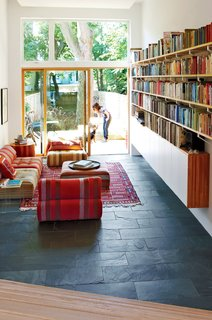 The living room is five steps down from the kitchen and office space and features textured black slate tile from Olympia Tile, Voyage Immobile sofas with Farniente collection upholstery (a wedding present from Flanders's mother) by Roche Bobois, and a rug from Turkmenistan the couple picked up in Jerusalem. The sliding glass doors are by Loewen and the glazing above is by Inline Fiberglass. Sawatzky relied on Wayne Arsenault for the custom millwork and carpentry.