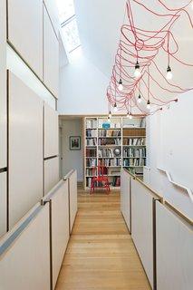 A dim Toronto Tudor gets an airy new look. The home's second-story hallway, which serves as an open office and library, was suffering from a severe lack of light. Lifting up one side of the old pitched roof made room for a linear skylight, which faces south to allow in as many rays as possible, and the modification transformed the top floor into a loftlike double-height space. Inexpensive detailing then added texture and scale: Simple plywood panels attached to cold-rolled-steel frames serve as guards along the stairs.