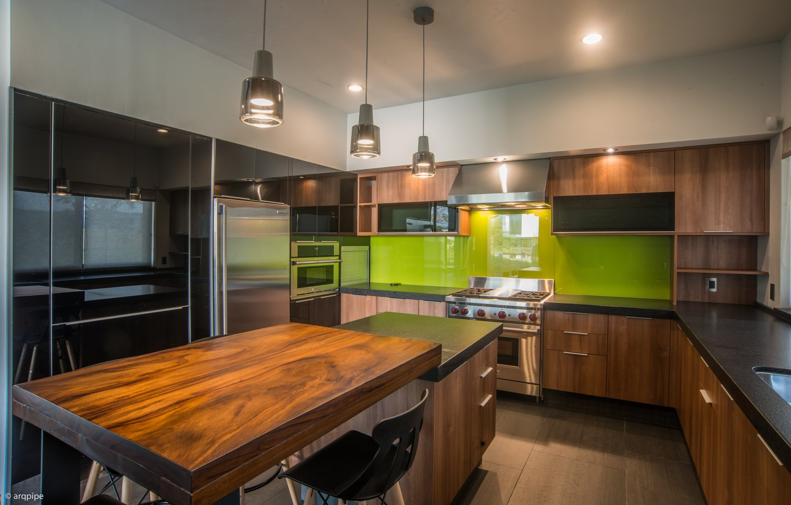 """A green backsplash adds a dash of color while the kitchen island sits under a series of pendant lights. The kitchen features Electrolux and Wolf appliances.  Search """"color story green"""" from A Home Rocks Out with Natural Stone, Concrete, and a Volcano"""