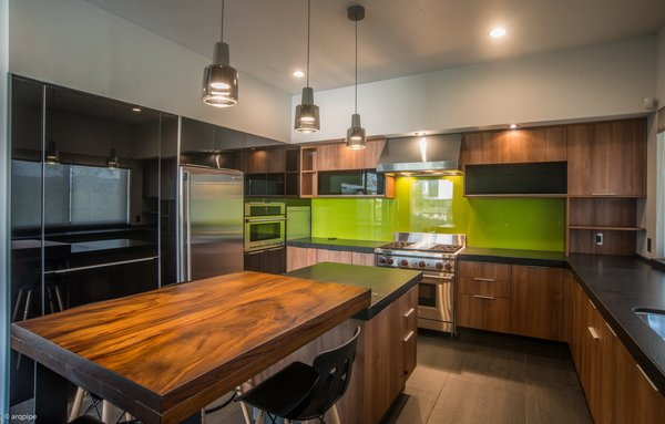 A green backsplash adds a dash of color while the kitchen island sits under a series of pendant lights. The kitchen features Electrolux and Wolf appliances.