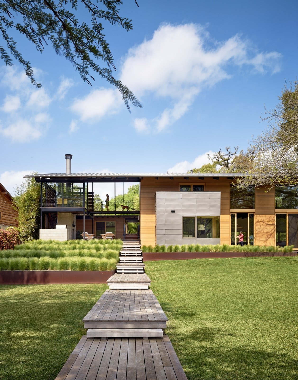"""Exterior, House Building Type, Flat RoofLine, and Wood Siding Material """"Consistent with the lakefront cabin charm, the owners liked the idea of accessing much of the house from outdoor porches and walkways,"""" says architect Ted Flato. Supplies from Dynamic Architectural Windows and Doors bring light in to the home's covered spaces.  Hog Pen Creek by Kelly Dawson"""