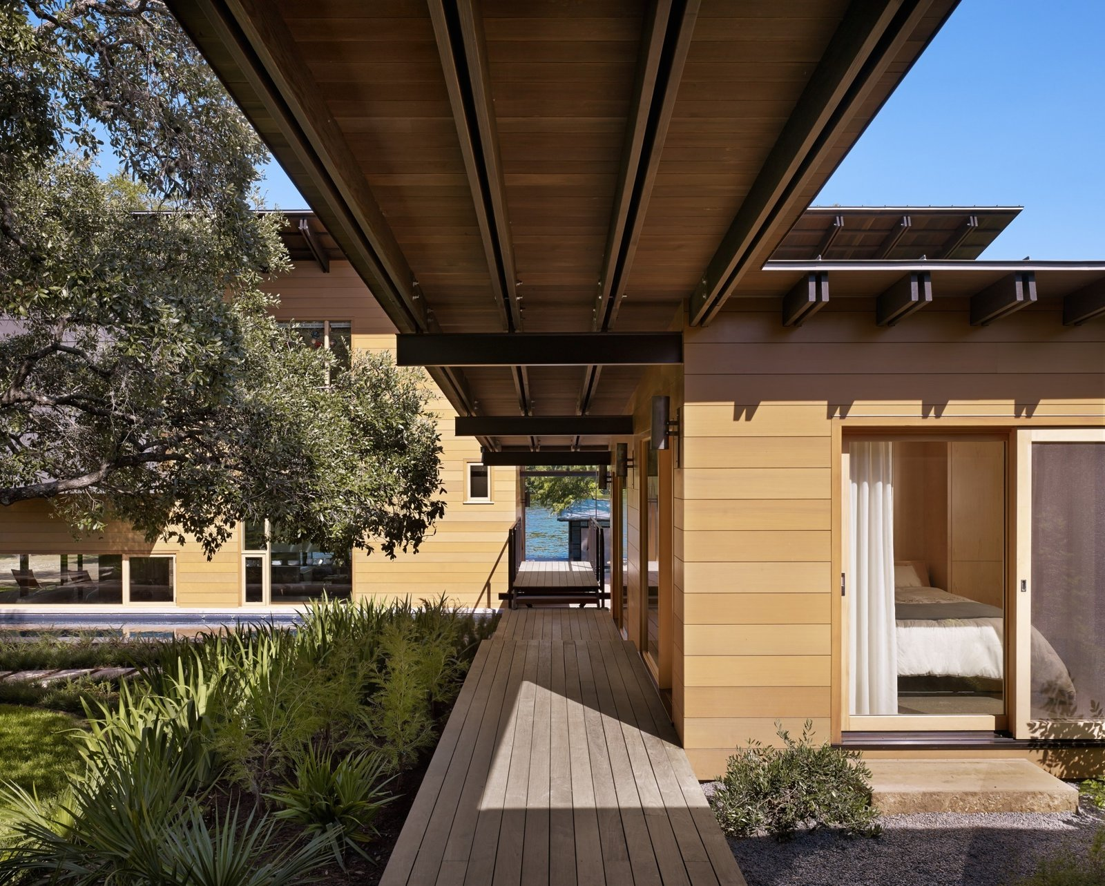 """""""The unique site-plan includes the main house, a two-story dog run, and a guest cabin,"""" Flato says. """"All are seamlessly stitched together by a grand boardwalk, making an arrival by boat or by car an equally engaging experience."""" Vertical grain Western red cedar acts as the exterior siding. Tagged: Outdoor, Wood Patio, Porch, Deck, Walkways, and Back Yard.  Hog Pen Creek by Kelly Dawson"""