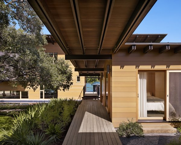 """""""The unique site-plan includes the main house, a two-story dog run, and a guest cabin,"""" Flato says. """"All are seamlessly stitched together by a grand boardwalk, making an arrival by boat or by car an equally engaging experience."""" Vertical grain Western red cedar acts as the exterior siding."""