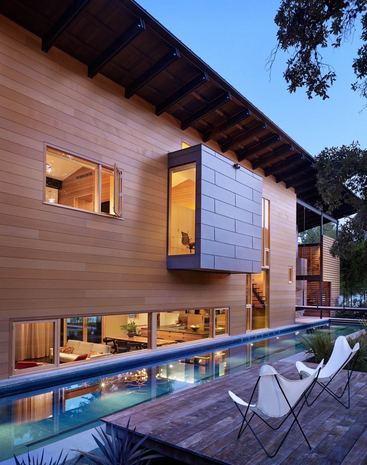 "Large, Wood, Small, Back Yard, Exterior, House, and Wood ""Exposing the craft and detail of the materials was a key part of the design,"" Flato notes. The texture of the house, he says, can be observed in the concrete retaining wall for the lap pool.  Exterior Wood Wood Photos from Hog Pen Creek"
