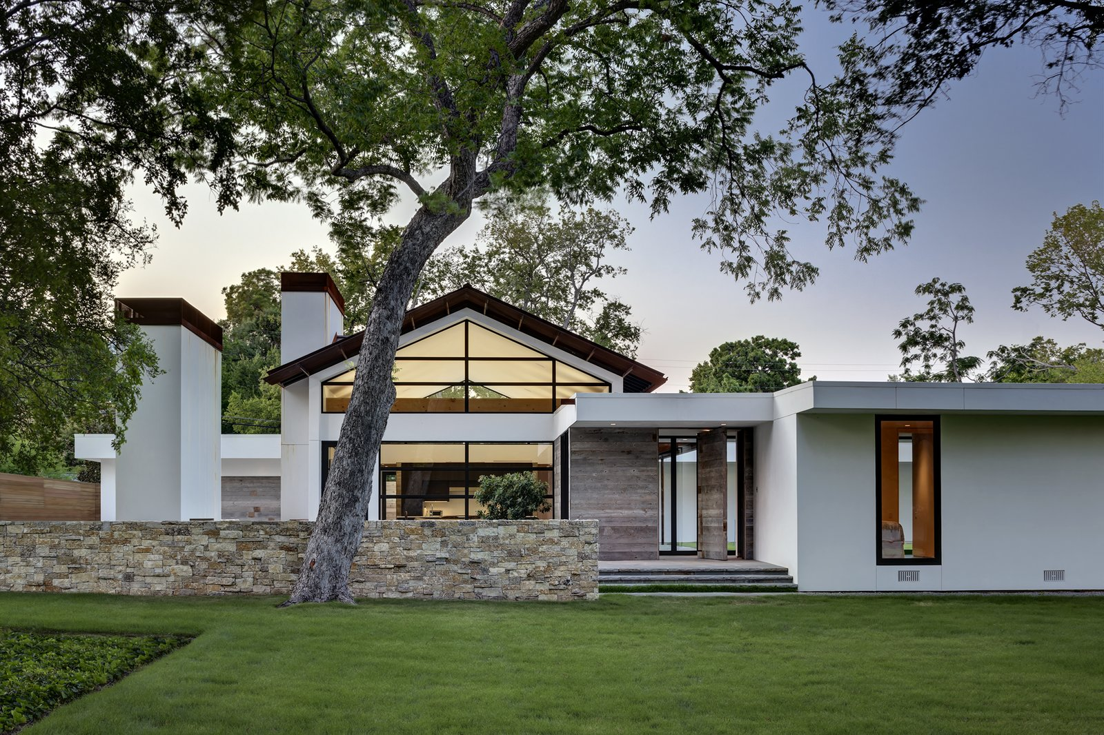 """The home's outer walls were dry-stacked with limestone cut from a Texas Granbury quarry, and its gabled roof was made with weathered Cor-Ten steel that emits the same maverick spirit as a Richard Serra sculpture. The freestanding fireplace just inside the courtyard was even salvaged from the old house's living room. Clean stucco walls contrast with the grass and trees, while reclaimed wood siding complement them.  Search """"cor ten steel"""" from Preston Hollow"""