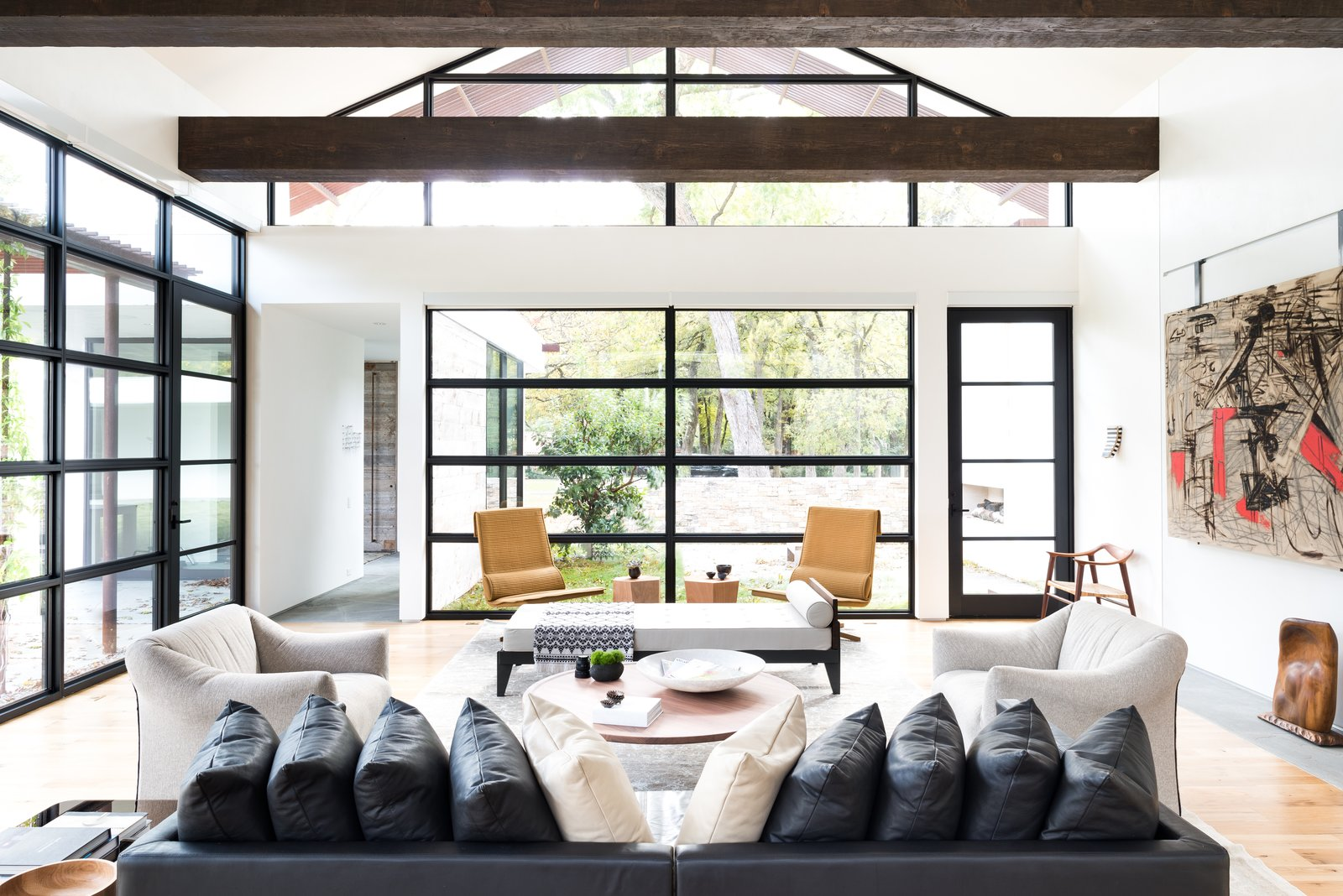 """For this project, the husband loved ultra-modern design, while the wife leaned towards a more traditional aesthetic. How to please both? """"Through the design process, we learned that their tastes were actually more closely aligned when we focused on the desired 'feel' of the home versus specific design details,"""" Field says.  He and his colleagues balanced rustic, exposed ceiling beams with elegant venetian plaster walls, and artful aluminum storefront windows with functional white oak plank flooring.  Shining Examples of Clerestory Windows by Luke Hopping from Preston Hollow"""