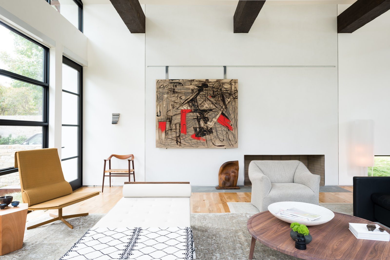 """Rice faced the same challenge of creating modern yet family-friendly interiors. He settled on a warm, muted palette with lots of texture. The space features a mix of comfortable seating with more unique, collectible pieces — like the Jean Prouvé daybed or Vincent van Duysen chairs by the window. """"I wanted the space to feel like a home rather than a museum,"""" Rice says.  Preston Hollow by Laura C. Mallonee"""