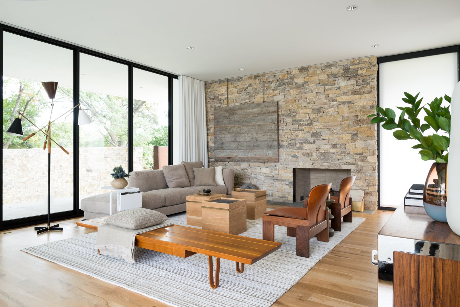 The family room boasts a Monza Triennale Floor Lamp by Gino Sarfatti and a Long John Bench by Edward Wormley, both from the 1950s, as well as a pair of '60s rosewood and leather '925' lounge chairs by Arfa and Tobia Scarpa. Pieces by Ludwig Mies van der Rohe and Alvar Aalto also fill the space.  Preston Hollow by Laura C. Mallonee