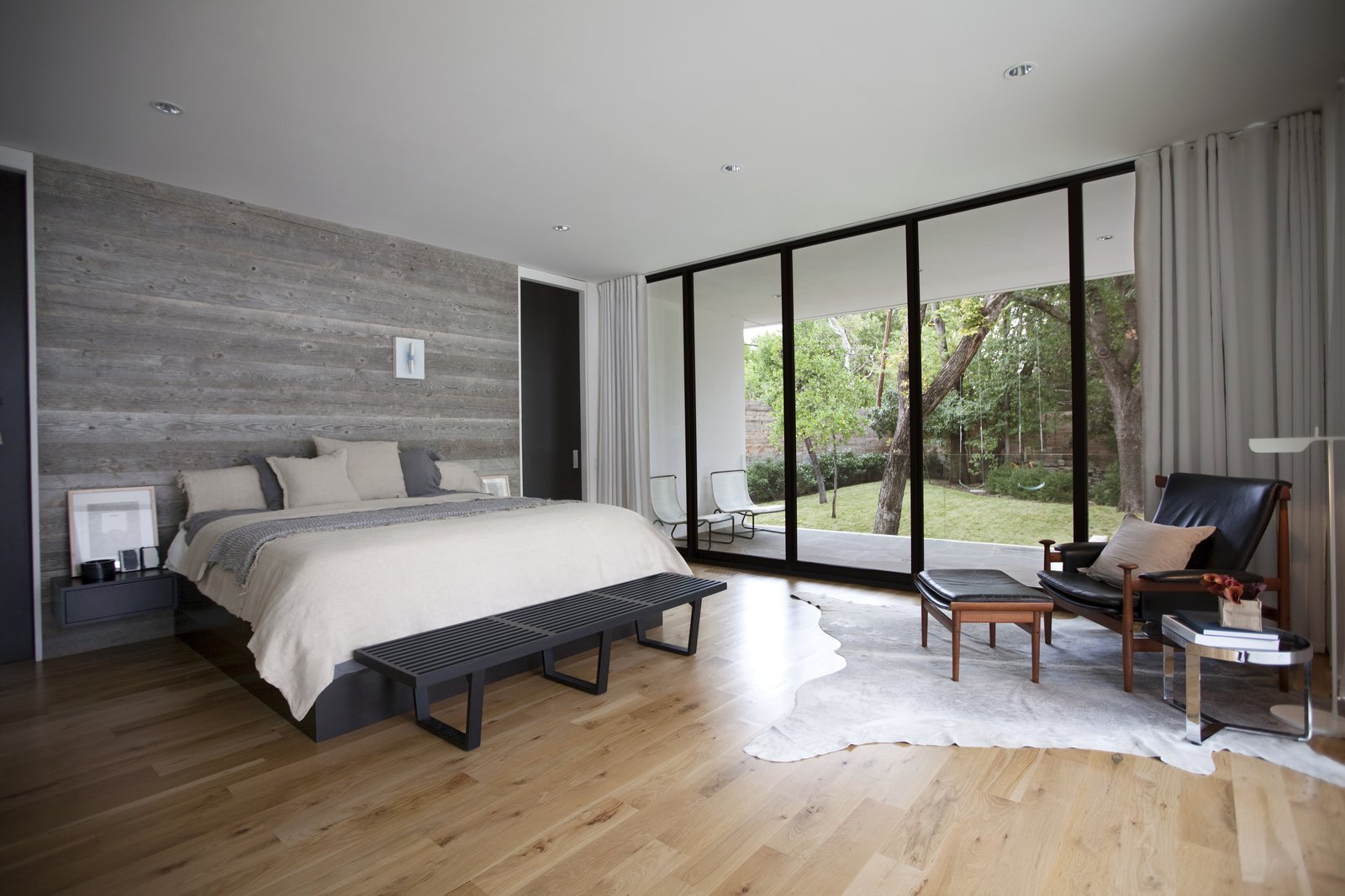 """In the master bedroom, the textural appeal of the reclaimed wood wall, bedding, and rug contrasts with the black leather of the African-inspired 'Bwana' Chair by Finn Juhl, which sits beside a 'TAB' reading lamp by Barber Osgerby. """"We believe a quality project is defined by the sum of all its parts versus any individual feature or design move,"""" Field says.  Preston Hollow by Laura C. Mallonee"""
