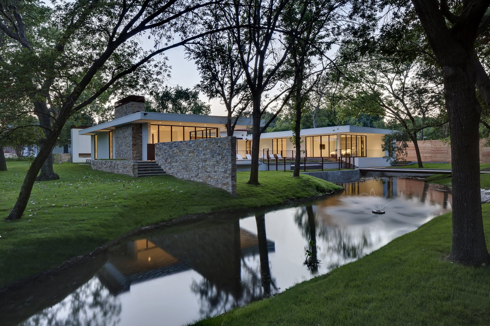 Privacy was important to the family, but they also wanted large expanses of glass through which to enjoy the trees and pond. The solution was a clever C-shaped courtyard plan that shields the home's open interior.  Preston Hollow by Laura C. Mallonee
