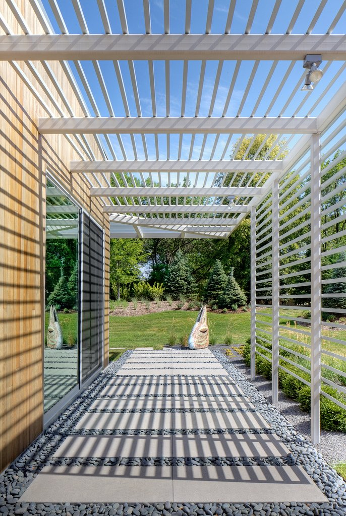 Tack Architects designed the house to frame views of the surrounding landscape. The trellis offers shading and controls the amount of daylight that shines inside (and creates a dramatic passage along the house's perimeter).  Omaha Art-Inspired House by Diana Budds from Statement-Making Trellises
