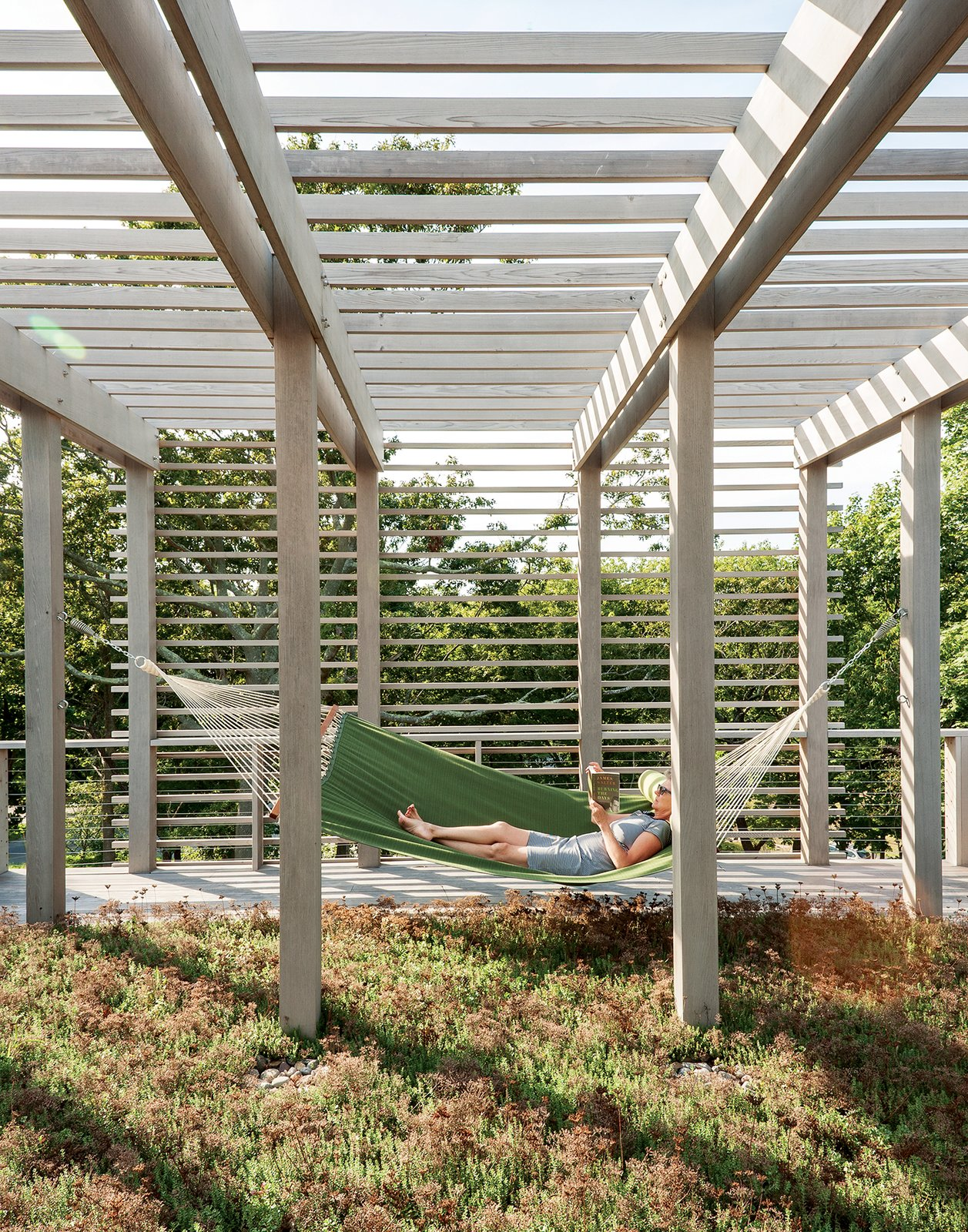 A second green roof is planted with sedum and plays host to one of the family's favorite spots: a hammock. Bentheim suggested adding a trellis overhead to soften and balance the appearance of the facade. Tagged: Outdoor and Back Yard.  Simple outdoor/indoor design from An Unconventional Prefab on Fishers Island