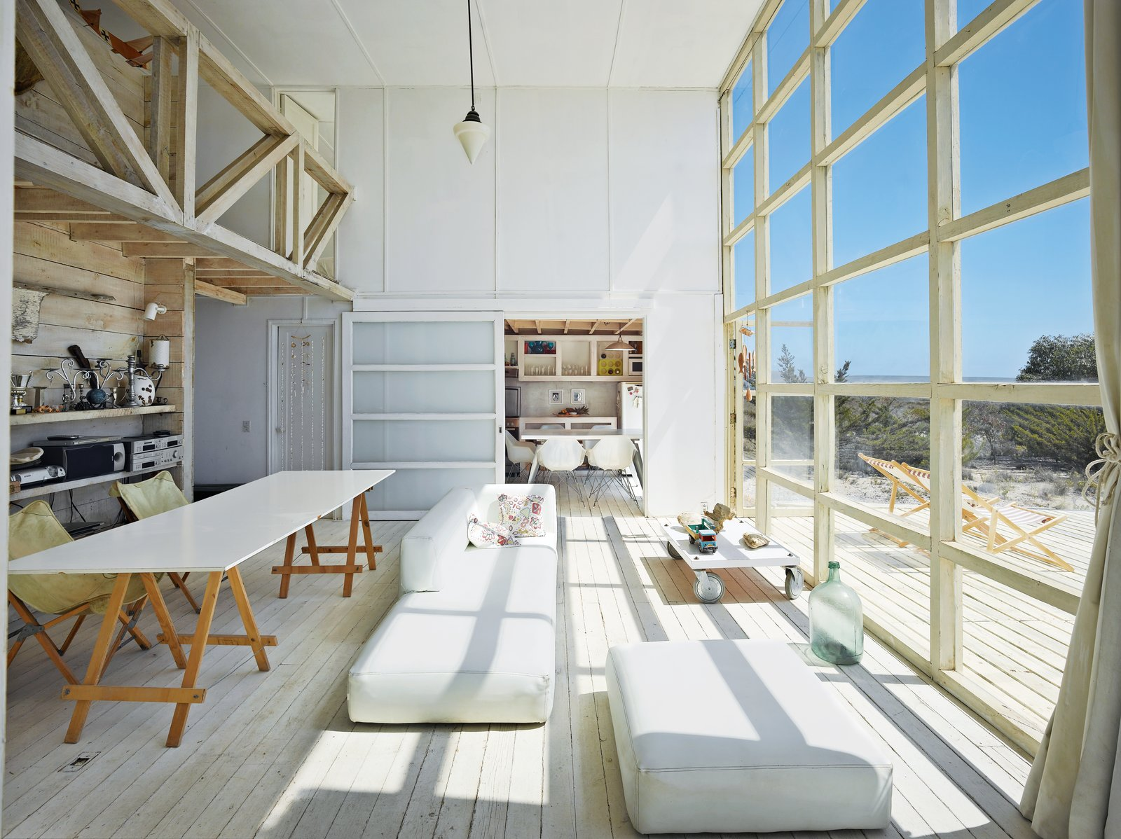 The northern facade, which faces the water, takes in the view via double-height windows in the main living room, plus terraces punched into the second floor.  Photo 1 of 2 in A Simple Geometric Bayfront Home in Chile