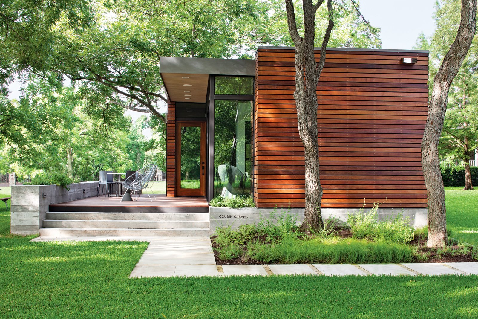 Exterior, House Building Type, and Wood Siding Material Landscape architect Tait Moring installed pavers around the structure's perimeter and kept the tree cover intact. Photo by: Kimberly Davis  Photo 4 of 6 in Small and Modern: A Family Lakeside Getaway in Texas