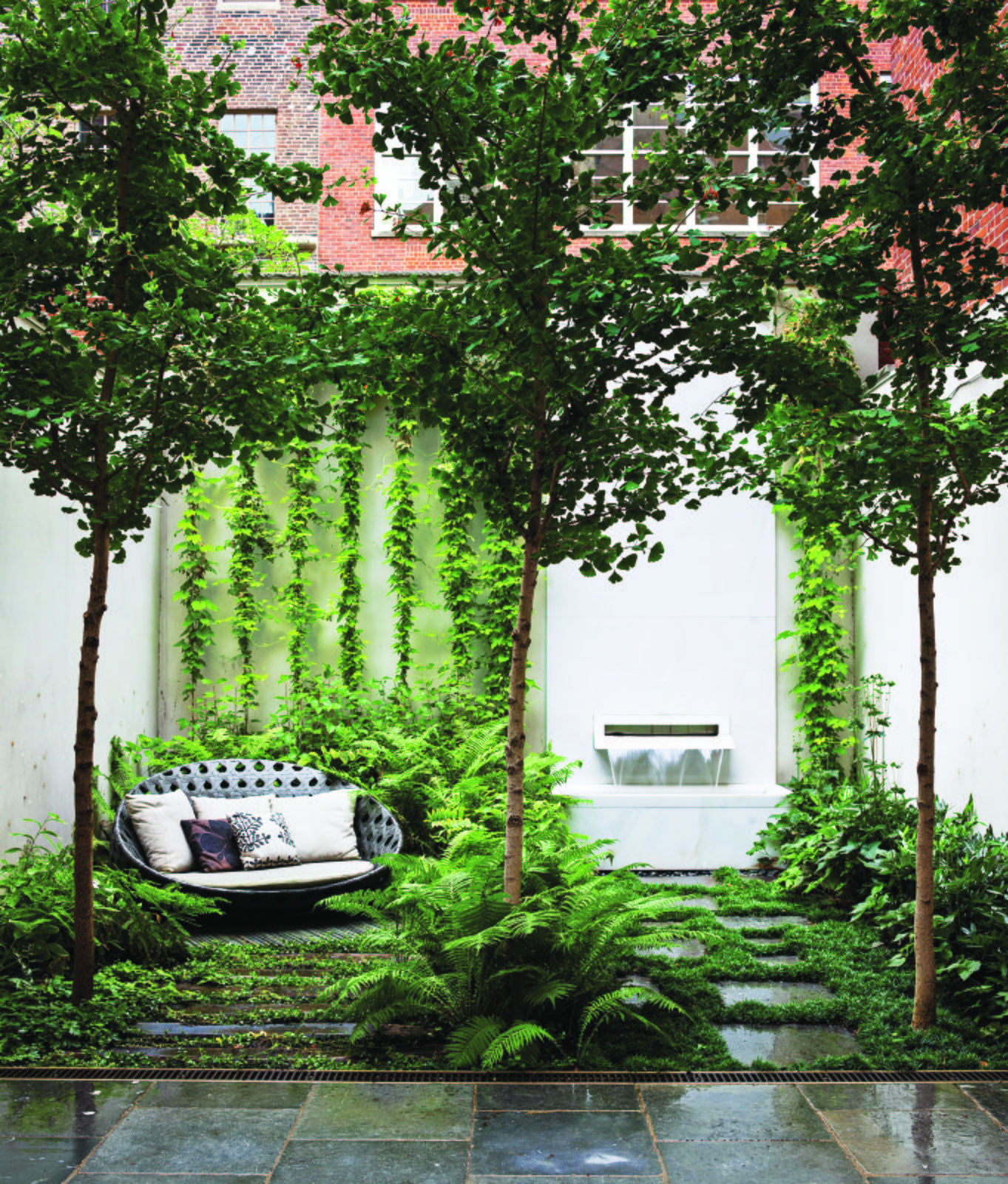 B&B Italia Outdoor's Canasta sofa, by Patricia Urquiola, shares a shady patch in the ground-floor Carnegie Hill garden with three ginkgo biloba trees, an existing fountain with an Italian marble spout designed by Thomas Woltz, and bluestone pavers. The terrace is filled with woodland greenery: Leucothoe, ostrich ferns, and lady ferns.  Photo 1 of 5 in Nelson Byrd Woltz Harnesses the Natural Elements