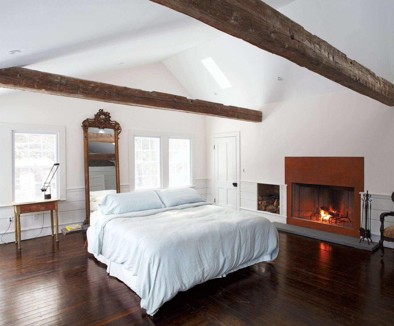 Bedroom, Bed, and Dark Hardwood Floor At a renovated farmhouse on a 19th-century homestead, a gas fireplace fronted in weathered steel warms up the lofty master bedroom, whose spare decor is framed with beams discovered in a Pennsylvania barn. The Tizio desk lamp is by Artemide.  Modern Designs Featuring Exposed Beams by Megan Hamaker from Hope Floats