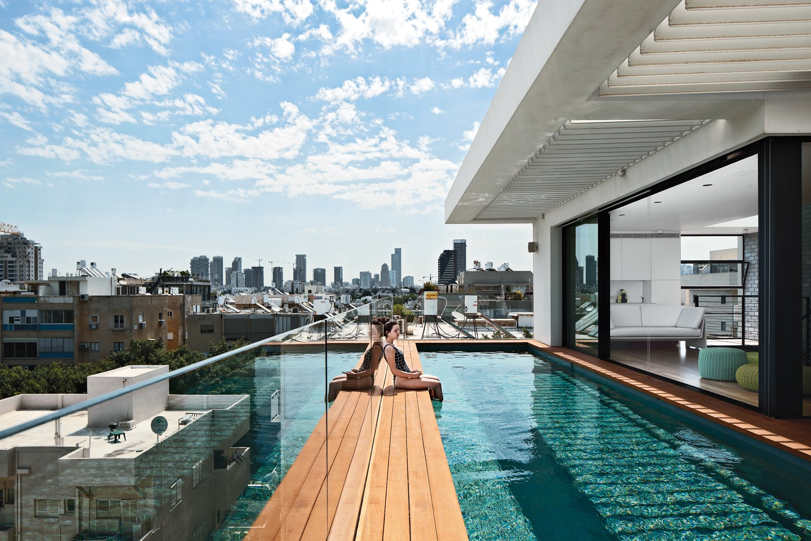 """Outdoor, Wood Patio, Porch, Deck, Small Patio, Porch, Deck, Swimming Pools, Tubs, Shower, Lap Pools, Tubs, Shower, Large Pools, Tubs, Shower, and Rooftop """"Tel Aviv is different from the rest of Israel. This is one of the most modern cities in the world."""" —Architect Pitsou Kedem  Top 10 Houses on Dwell This Week November 21, 2013 by Jami Smith from Modern High-Rise Town House in Tel Aviv"""