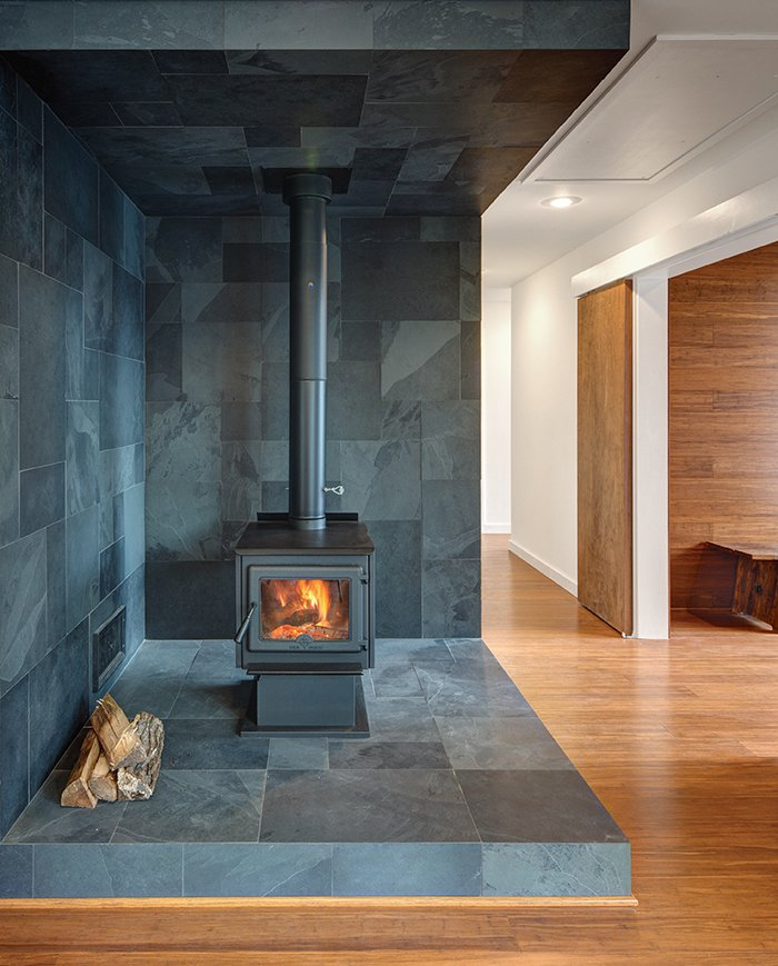Vermont slate covers the area around the True North wood stove.  Wide-plank Yanachi Carbonized Strand Woven Bamboo covers the floors.  Photo 3 of 6 in How to Build an Off-the-Grid Cabin in Arkansas for just over $118,000