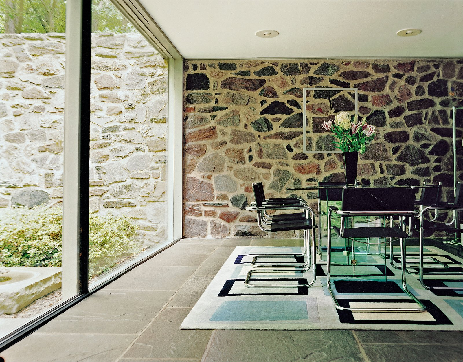 Dining Room, Chair, Table, Rug Floor, and Slate Floor Three stark planes make the dining room a place of sun and shadow: a wall of rock, a floor of bluestone, and a sheer slice of glass. Further adding to the unity of the house, the tubular steel dining chairs were also designed by Breuer.  marcel breuer from Marcel Breuer Hooper House II