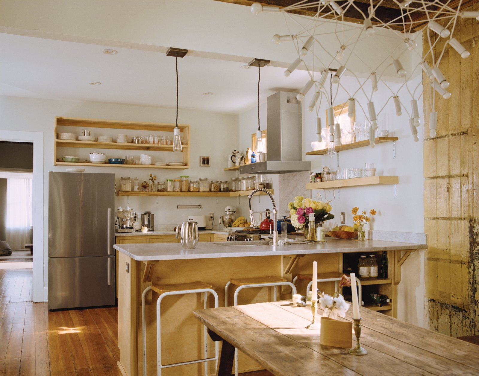 The trio of pendant lamps hanging above the counter came from Schoolhouse Electric Co. and were reworked by Peyton Avrett to fit the width of the header beam to which they are attached. The bar stools were gifted from a friend.  Photo 9 of 18 in Raise High the Roof Beams
