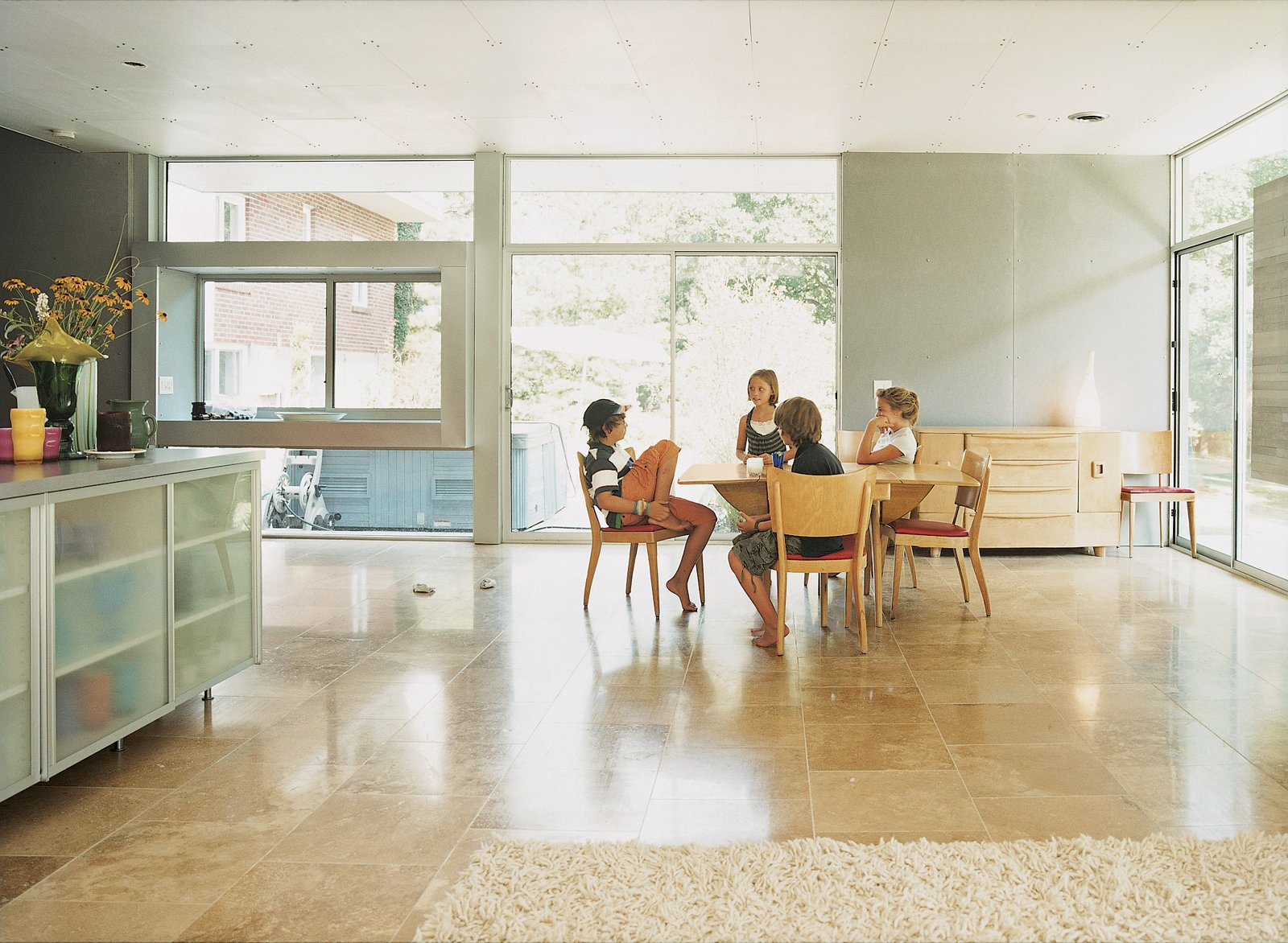 The kids gather around the Heywood-Wakefield dining set, which Terry purchased from Mainly Art in Cincinnati. The flooring in the kitchen and living area is honed travertine from The Great Indoors.  Photo 2 of 6 in Modern Across America: Cincinnati, Ohio from Home Schooled