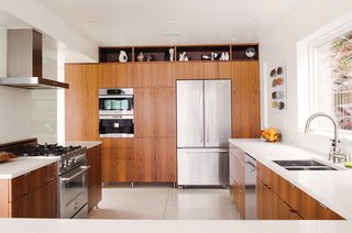"""The new kitchen includes walnut cabinetry, a Bertazzoni range, a Futuro Futuro range hood, a Nespresso coffee system and convection oven from Miele, and a Jenn-Air refrigerator. The faucet is by Grohe; the sink is from Ticor. """"The kitchen is in the same spot as it was,"""" Julien says. """"We kept the plumbing fixture locations, but enlarged it."""""""