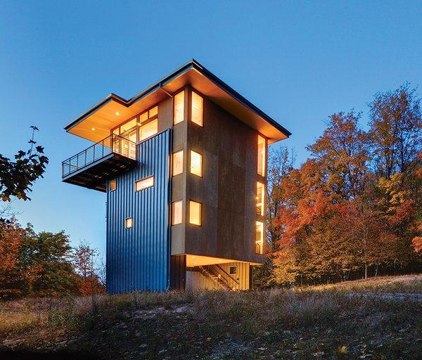 "Rough-sawn plywood and standing-seam metal siding clad the house. ""In cabins, we like to use undressed materials, which lend themselves to the simplicity of the structure,"" says architect Tom Lenchek."