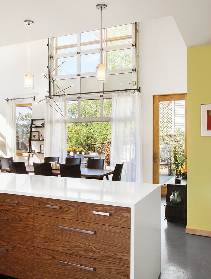 A Batons chandelier from LBL Lighting hangs over the dining table. A garage-style door by Overhead Door opens onto a patio that gets plenty of use when the weather cooperates.  60+ Modern Lighting Solutions by Dwell from Cost-Effective Family Home in Pittsburgh