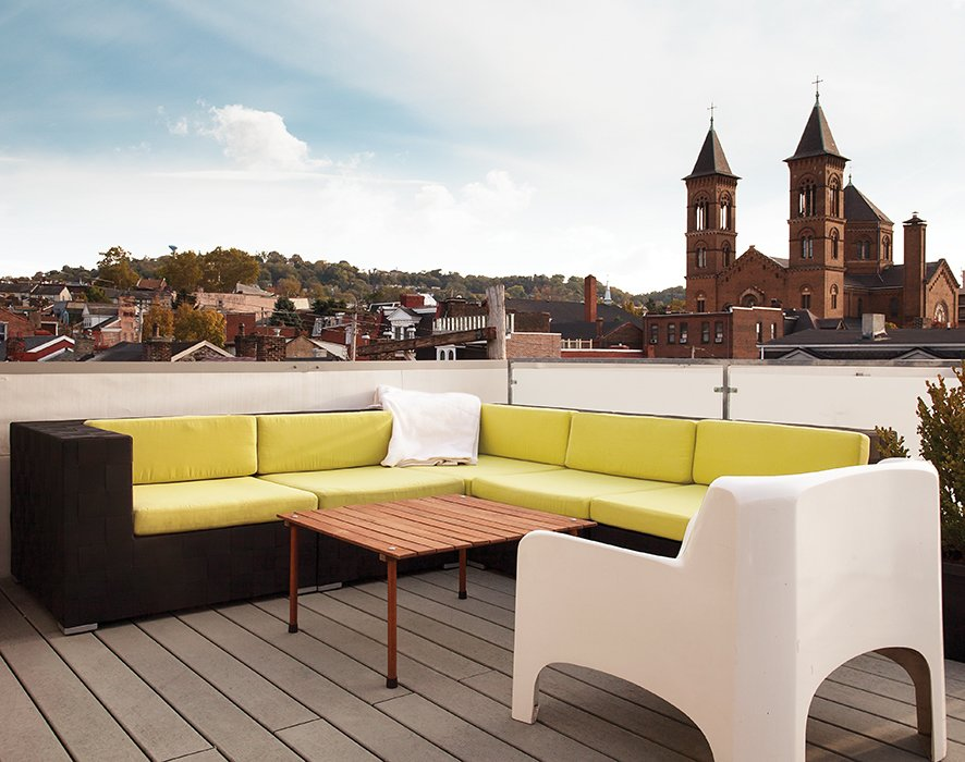 "The roof deck, with views of the nearby St. Augustine church and beyond to downtown Pittsburgh, features partially recycled plastic decking from Rhino Deck and a custom galvanized-steel railing with frosted Plexiglas panels. ""Pittsburgh's one of those cities that if you grew up here, it has a draw that pulls you back,"" Moss says.  Photo 5 of 8 in Cost-Effective Family Home in Pittsburgh"